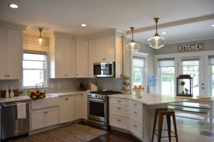 White Cabinets with Brass hardware knobs and cup pulls Farmhouse sink Wood to tile floor transition hexagon