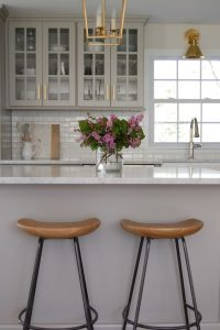 Glam Gray Kitchen cabinets with brass hardware and fixtures wood and metal saddle counter stools
