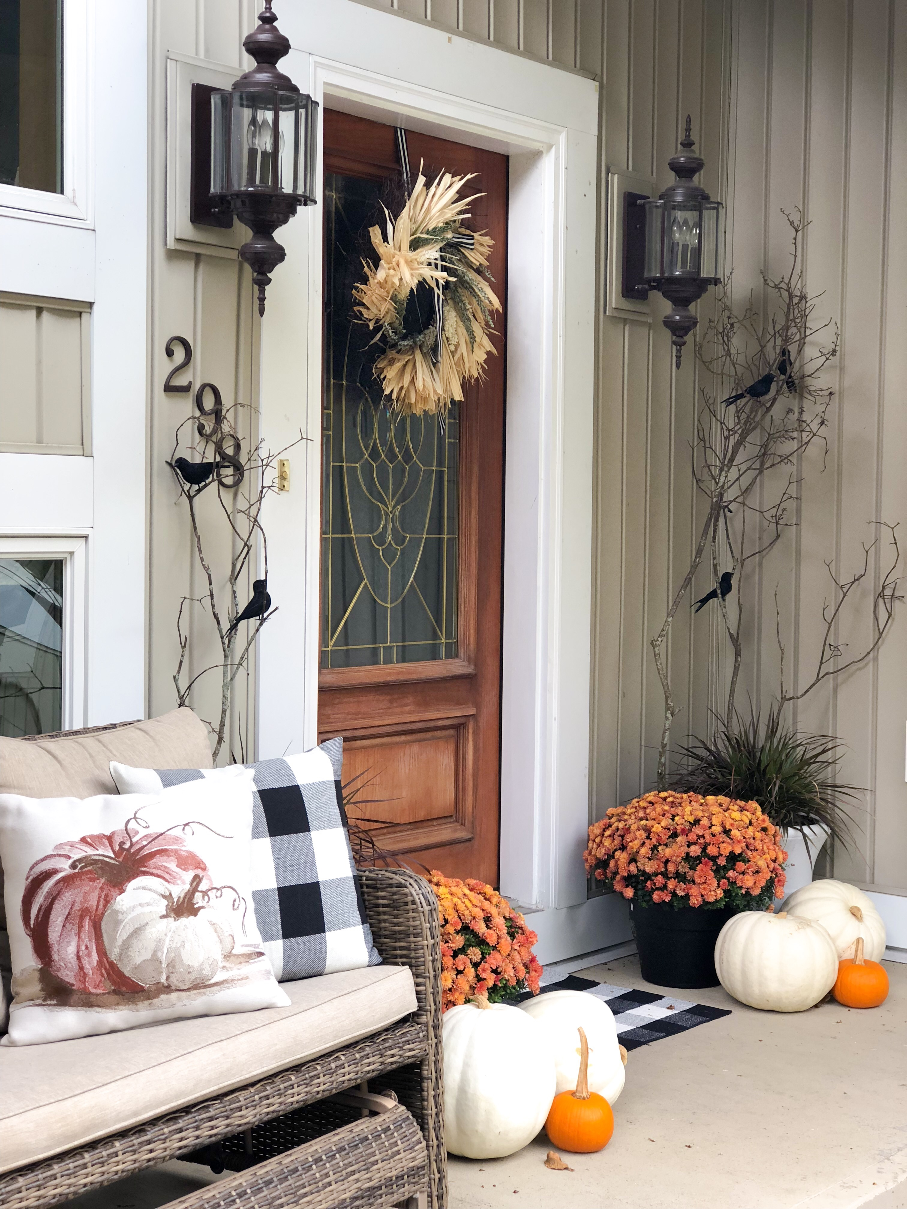 Orange Mums, white pumpkins with straw wreath, tree branches with black crows and buffalo check pillow and pumpkin pillow on bench.