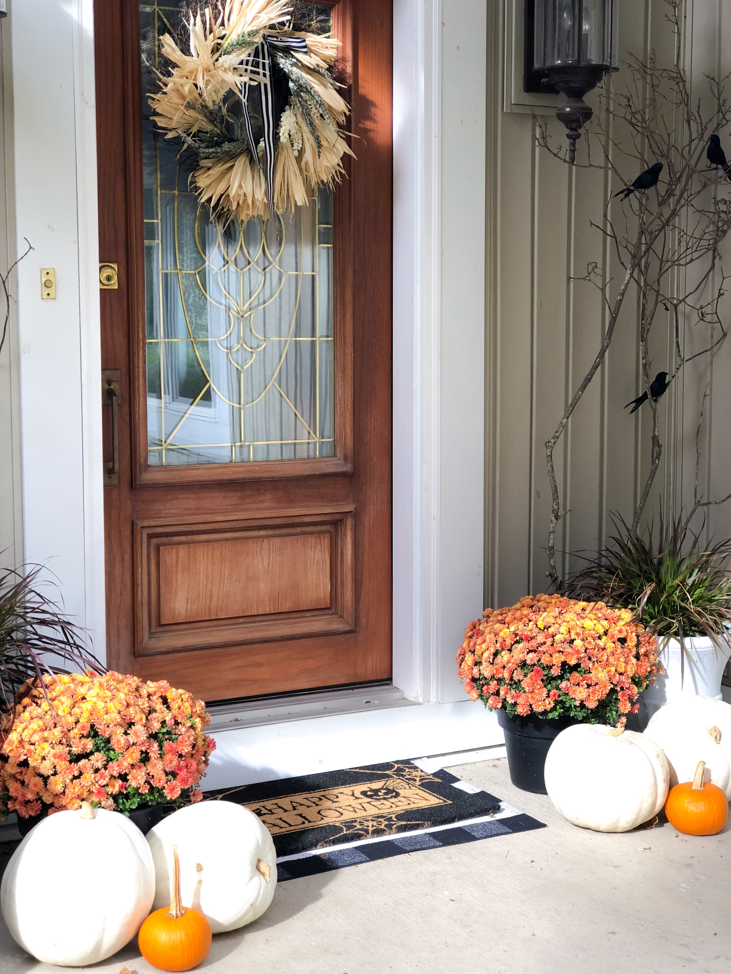 Orange Mums with white pumpkins, straw wreath with black and white ribbon, black and white buffalo check doormat and tree branches with black crows