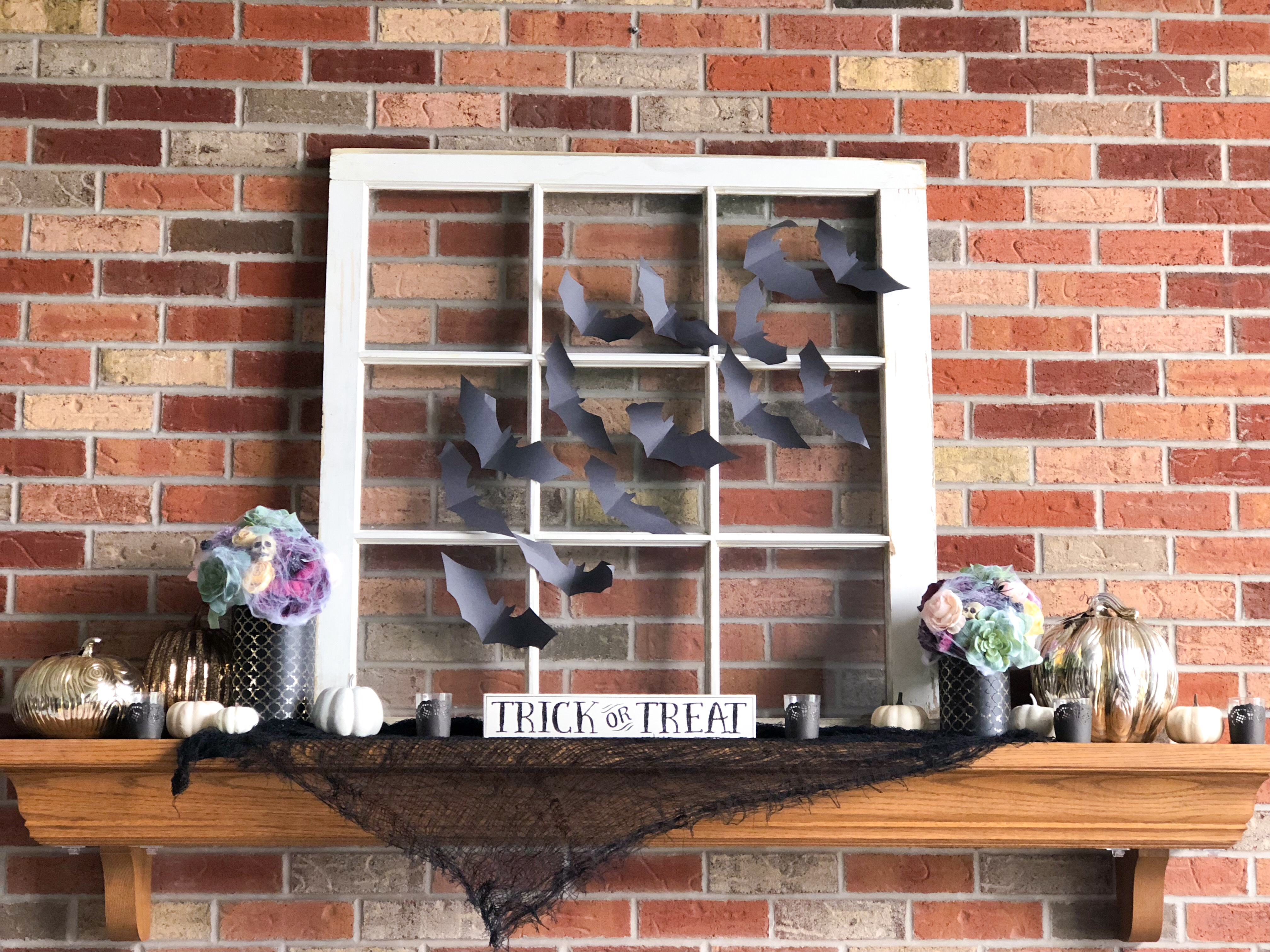 Black cheese cloth draped over mantle with trick or treat sign, old window covered in black paper bats with colorful floral arrangements with skulls and spiders