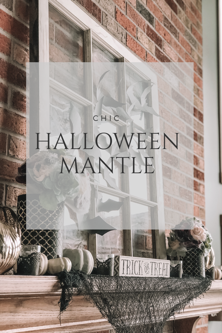 Mantle with Halloween decor with black lace votives, burgundy floral arrangements and black paper bats on an antique window